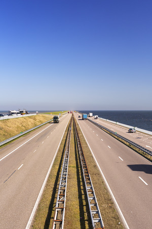 noord: Traffic on the Afsluitdijk on a sunny day in The Netherlands. The Afsluitdijk is a dike over 32km damming off the former Zuiderzee, a salt water inlet of the North Sea.