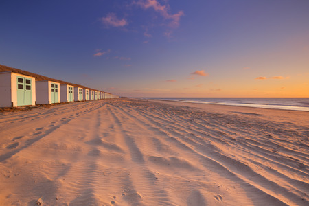 beach scene: A row of beach huts on a beach on the island of Texel in The Netherlands. Photographed at sunset.