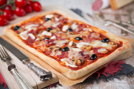 Homemade rectangular pepperoni pizza on a rustic table with ingredients. Reklamní fotografie