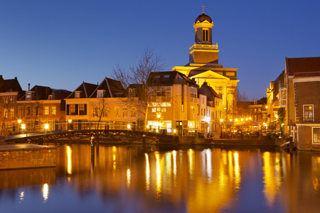 A canal with the Hartebrug church in Leiden, The Netherlands at night.