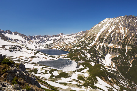 lingering: Dolina Piciu Staww Five Lakes Valley in the Polish Tatra Mountains in spring, with the last snow still lingering on the mountains.