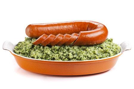 A dish with 'Boerenkool met worst' or kale with smoked sausage, a traditional Dutch meal. Isolated on white.