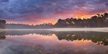 Reflections of sunrise at a quiet lake. Photographed at the Henschotermeer in The Netherlands. Reklamní fotografie