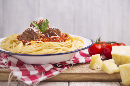 grated parmesan cheese: A plate with spaghetti with meatballs, topped with some grated parmesan cheese and basil.