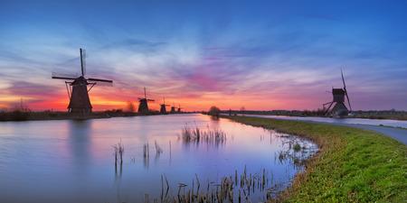 Moulins à vent hollandais traditionnels avec un ciel coloré juste avant le lever du soleil. Photographié à la célèbre Kinderdijk.