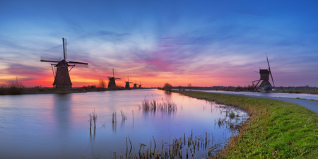 water's: Traditional Dutch windmills with a colourful sky just before sunrise. Photographed at the famous Kinderdijk.