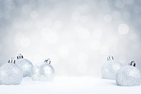 Silver Christmas baubles on snow with defocused silver and white lights in the background. Shallow depth of field. Foto de archivo