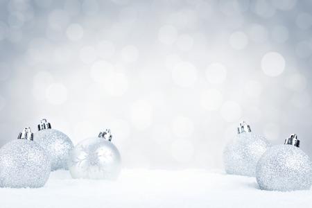 Zilveren kerstballen op sneeuw met onscherpe zilver en witte lichten op de achtergrond. Ondiepe scherptediepte.