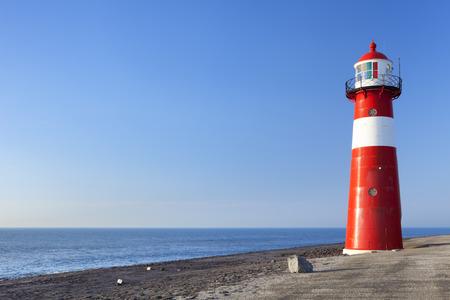 맑고 푸른 하늘 아래 바다에서 빨간색과 흰색 등 대. Zeeland, 네덜란드에서에서 Westkapelle 근처 촬영 스톡 콘텐츠