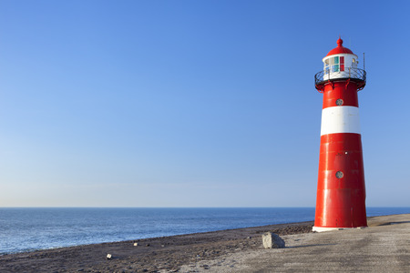 A red and white lighthouse at sea under a clear blue sky. Photographed near Westkapelle in Zeeland, The Netherlands. Stock Photo