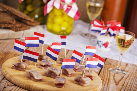 indoor photo: Herring with gherkins and pickled onions, served with a shot of korenwijn (grain wine). A traditional Dutch delicacy, with peak season at the end of spring when the first young herring is brought in from sea. Stock Photo
