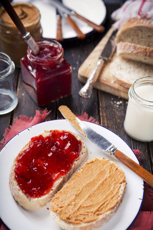 peanut butter and jelly sandwich: Peanut butter and jelly sandwich on a rustic table.