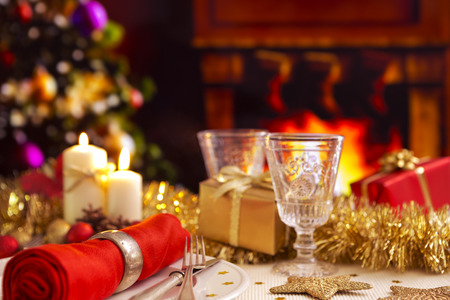 A romantic Christmas dinner table setting with candles and Christmas decorations. A fire is burning in the fireplace and Christmas stockings are hanging on the mantelpiece. A Christmas tree is standing next to the fireplace in the background.