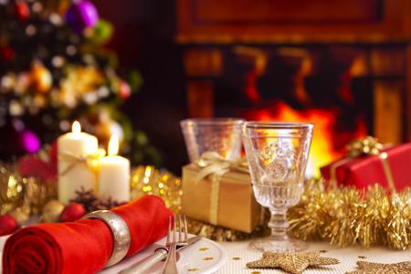 Un dîner de Noël décor de table romantique avec des bougies et des décorations de Noël. Un feu brûle dans la cheminée et des bas de Noël sont accrochés sur la cheminée. Un arbre de Noël est debout à côté de la cheminée dans l'arrière-plan.