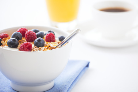 breakfast cup: A healthy breakfast with muesli, fresh berries, orange juice and a cup of coffee. Shallow depth of field, focus on berries and muesli. Stock Photo