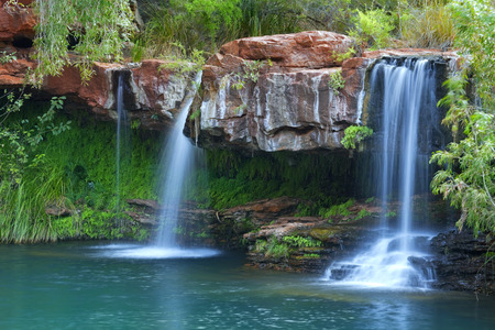 A small waterfall flowing into the Fern Pool in Karijini National Park, Western Australia.
