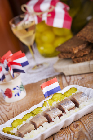 dutch culture: Herring with gherkins and pickled onions, served with a shot of korenwijn (grain wine). A traditional Dutch delicacy, with peak season at the end of spring when the first young herring is brought in from sea. Stock Photo