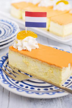 Een oranje Tompouce, traditionele Nederlandse gebak, op een witte achtergrond. De oranje kers op de Tompouce is typisch voor King's Day ('Kongingsdag') op 27 april.