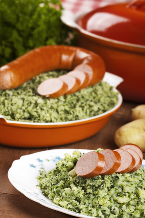 worst: A rustic table with a plate with Boerenkool met worst or kale with smoked sausage, a traditional Dutch meal.