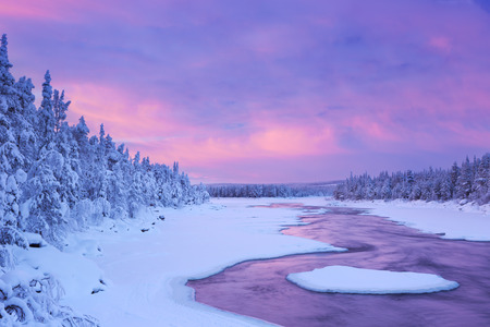 A rapid in a river in a wintry landscape. Photographed at the ijkoski rapids in the river in Finnish Lapland Muonionjoki at sunrise. Stock Photo
