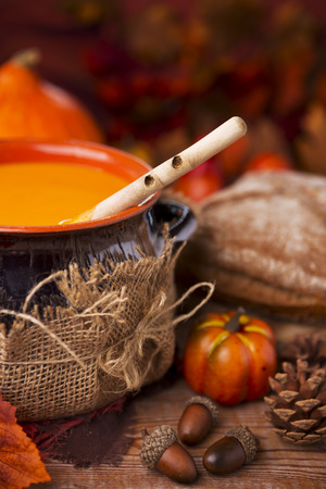 soup bowl: A pot of homemade creamy pumpkin soup on a rustic table with autumn decorations. Stock Photo