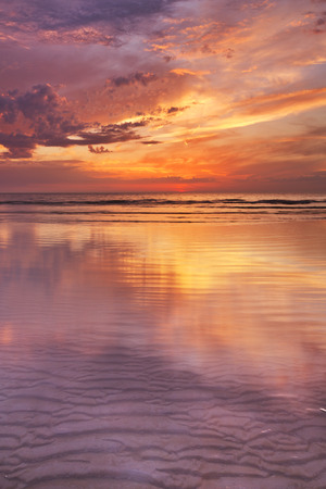 Spectacular sunset colours over sea reflected in the water at low tide. Photographed on the island of Texel, The Netherlands.