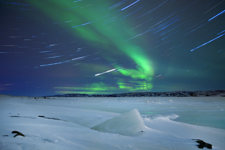 Spectacular aurora borealis northern lights over a frozen lake in northern Norway.