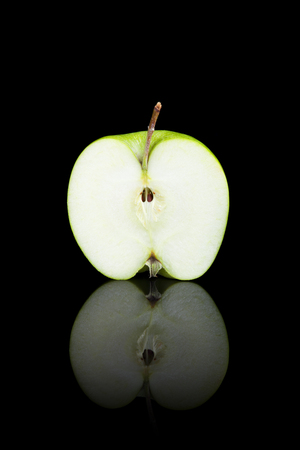 cut: A cut green apple on a black reflective background.