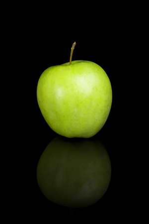 reflective: A green apple on a black reflective background.