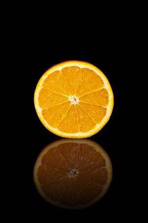 A cut orange on a black reflective background.