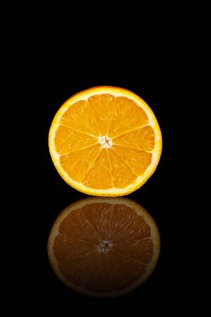 reflective: A cut orange on a black reflective background.
