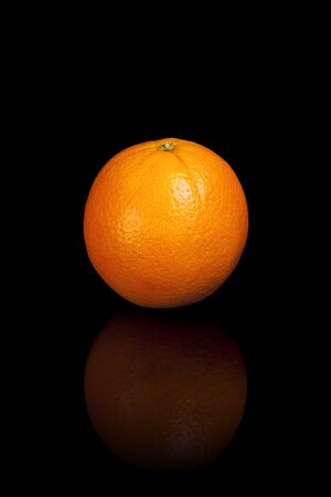 reflective: An orange on a black reflective background.