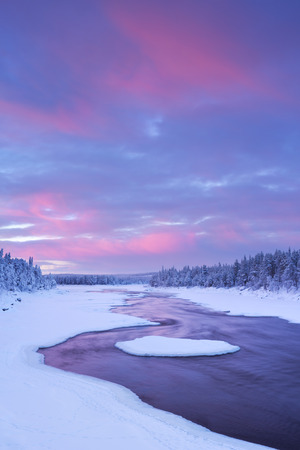 water's edge: A rapid in a river in a wintry landscape. Photographed at the ijkoski rapids in the river in Finnish Lapland Muonionjoki at sunrise. Stock Photo