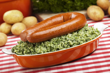 dutch: A rustic table with a dish with Boerenkool met worst or kale with smoked sausage, a traditional Dutch meal.