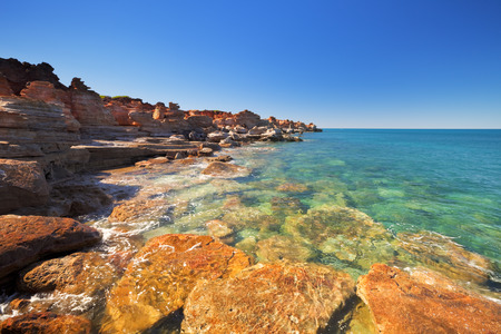 clear day: Red cliffs at Gantheaume Point, Broome, Western Australia on a bright and sunny day. Stock Photo