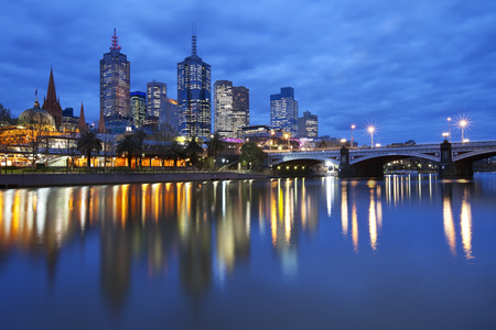 The skyline of Melbourne, Australia with Flinders Street Station and the Princes Bridge from across the Yarra River at night.