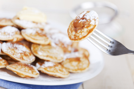 'Poffertjes': little Dutch pancakes with butter and powdered sugar. A fork picking one 'poffertje' from the plate and lifting it up. Shallow depth of field, focus on the single 'poffertje' on the fork. Фото со стока - 44238358