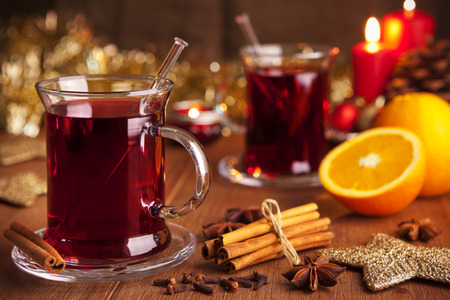 food photography: A glass with mulled wine or glhwein on a rustic table with ingredients and Christmas decorations.