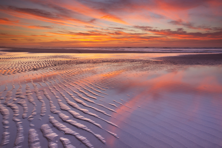 Beautiful sunset and reflections on the beach at low tide. Reklamní fotografie - 44238661