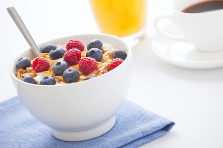 A healthy breakfast with muesli, fresh berries, orange juice and a cup of coffee. Shallow depth of field, focus on berries and muesli. Reklamní fotografie