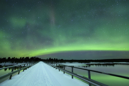 arctic waters: Spectacular aurora borealis northern lights over a bridge and a river in a snowy winter landscape in Finnish Lapland.