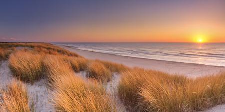 Hohe Dünen mit Dünengras und eine breite Strand unten. Bei Sonnenuntergang auf der Insel Texel in Holland fotografiert. Standard-Bild
