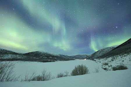 naturally: Spectacular aurora borealis northern lights over a snowy winter landscape in Finnish Lapland.