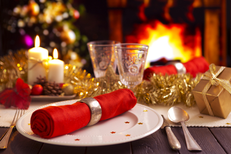 A romantic Christmas dinner table setting with candles and Christmas decorations.