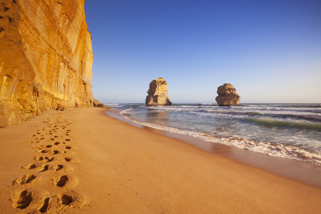 apostles: Footsteps on the beach at the Twelve Apostles along the Great Ocean Road, Victoria, Australia. Photographed at sunset.
