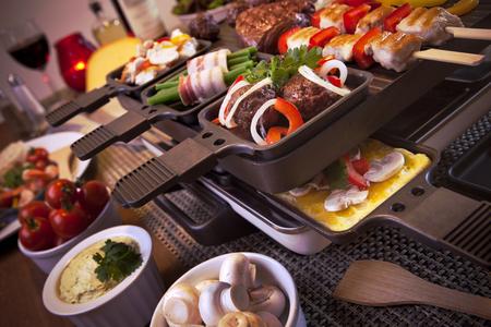 Raclette suisse ou la variante néerlandaise 'gourmetten'. Une table remplie avec des ingrédients pour un plat qui est généralement servi le soir de fête comme Noël ou le Nouvel An aux Pays-Bas.