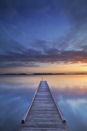 jetty: A small jetty on a lake at sunrise. Photographed near Amsterdam in The Netherlands. Stock Photo