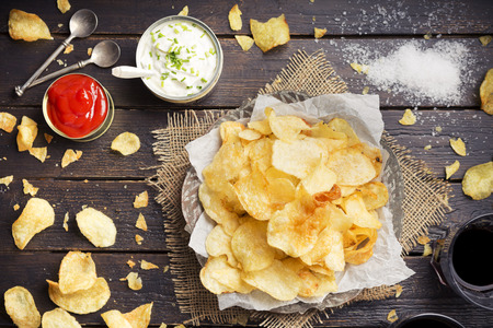 messy kitchen: Potato chips with dipping sauces on a rustic table.