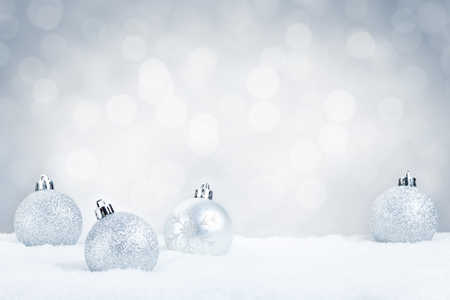 Silver Christmas baubles on snow with defocused silver and white lights in the background. Shallow depth of field. Reklamní fotografie - 44557339