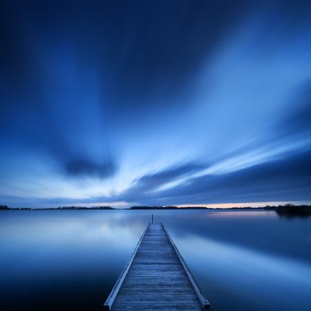 Een kleine steiger op een meer in de buurt van Amsterdam in Nederland. Een langzame sluitertijd werd gebruikt om de beweging van de wolken aan de hemel te zien. Gefotografeerd in de vroege ochtend.